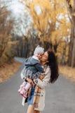 Juego de la mamá de la mujer joven con poca hija en el camino del parque del otoño imagenes de archivo