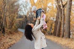 Juego de la mamá de la mujer joven con poca hija en el camino del parque del otoño fotografía de archivo