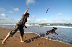 Juego de la muchacha con el perro Foto de archivo