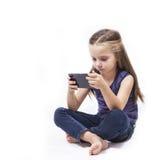 Juego de la muchacha con su smartphone Imágenes de archivo libres de regalías
