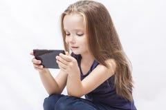 Juego de la muchacha con su smartphone Imagenes de archivo