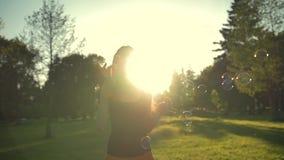 Juego de la mujer joven con las burbujas de jabón, al aire libre divirtiéndose almacen de video
