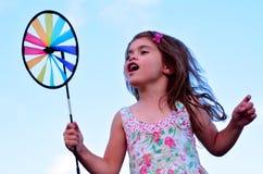 Juego de la niña con el molino de viento del juguete del molinillo de viento imágenes de archivo libres de regalías