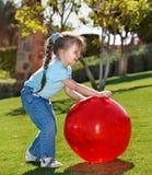 Juego de la niña con la bola en el parque Foto de archivo libre de regalías