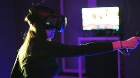 Juego de la realidad virtual del juego 3D de la mujer Lanzamientos con los reguladores en un juego de la pistola VR Muchacha que  almacen de metraje de vídeo
