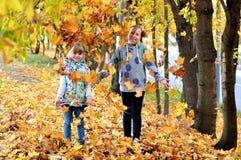 Juego de las chicas jóvenes al aire libre en la estación del otoño fotografía de archivo libre de regalías