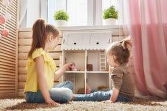 Juego de las muchachas con la casa de muñecas foto de archivo
