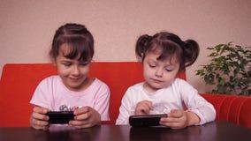 Juego de las niñas con un teléfono móvil metrajes