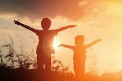 Juego de las siluetas del niño pequeño y de la muchacha en la puesta del sol Foto de archivo