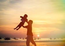 Juego de las siluetas del padre y del hijo en la puesta del sol Foto de archivo
