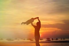 Juego de las siluetas del padre y del hijo en la puesta del sol Imágenes de archivo libres de regalías