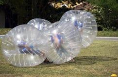 Juego de los adolescentes en el juego del topetón de la burbuja al aire libre Fotos de archivo