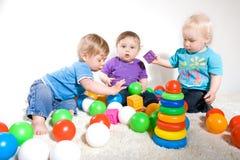 Juego de los bebés con los juguetes Imagen de archivo