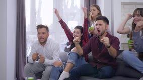 Juego de los deportes de la televisión, amigos emocionados de las fans con las novias que miran la competencia de deportes disfru metrajes