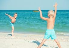 Juego de los hermanos con el disco volador en la playa Vacaciones de verano fotografía de archivo libre de regalías