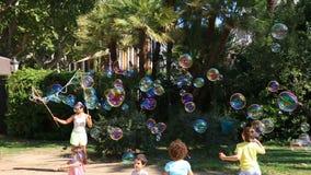 Juego de los niños con las burbujas Porciones de burbujas en el parque en Barcelona, España el 23 de agosto de 2015 metrajes