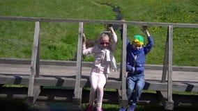 Juego de los niños en el puente sobre corriente almacen de metraje de vídeo