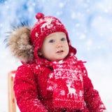 Juego de los niños en nieve Paseo del trineo del invierno para los niños Fotografía de archivo libre de regalías