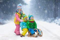 Juego de los niños en nieve Paseo del trineo del invierno para los niños imagen de archivo libre de regalías