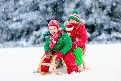 Juego de los niños en nieve Paseo del trineo del invierno para los niños fotografía de archivo