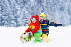 Juego de los niños en nieve Paseo del trineo del invierno para los niños fotos de archivo libres de regalías