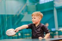 Juego de los tenis de mesa, muchacho que juega la pelota de tenis en el pasillo del tenis Imagen de archivo libre de regalías