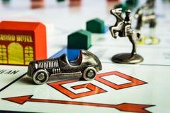 Juego de mesa del monopolio - el símbolo del coche siguió de cerca por otros símbolos fotografía de archivo libre de regalías