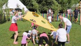 Juego de niños con el animador en el patio, animadores en el trabajo que juega con los niños en festival étnico en el aire abiert almacen de video