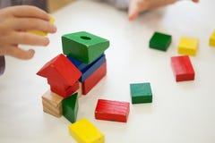Juego de niños con formas de madera coloreadas del ladrillo Fotografía de archivo libre de regalías