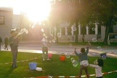 Juego de niños con las burbujas de jabón grandes en un césped verde cerca del V Imágenes de archivo libres de regalías