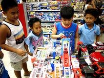 Juego de niños con los juguetes en una tienda de juguete en alameda de la ciudad del SM en la ciudad de Taytay, Filipinas Imagenes de archivo