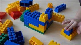 Juego de niños con los ladrillos plásticos coloreados almacen de video