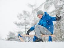 Juego de niños en nieve con el trineo Imagenes de archivo
