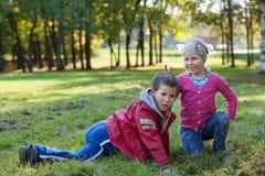 Juego de niños feliz y satisfecho junto en parque del otoño Fotos de archivo