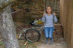 Juego de niños gitano de la muchacha en el oscilación en jardín sucio Fotografía de archivo libre de regalías