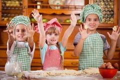 Juego de niños joven divertido tres con una pasta en la cocina Foto de archivo libre de regalías