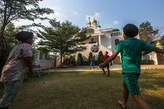 Juego de niños tailandés en bola cerca de la iglesia ortodoxa rusa Imagenes de archivo