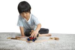 Juego de ni?os con un dise?ador del juguete en el piso del cuarto del ` s de los ni?os Cabritos que juegan con los bloques colori imágenes de archivo libres de regalías