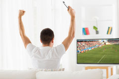 Juego de observación del fútbol o de fútbol del hombre feliz en la TV imagenes de archivo
