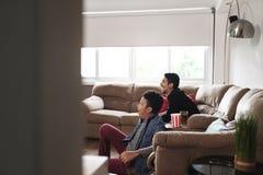 Juego de observación de los deportes de los pares gay felices en la TV en casa imagen de archivo libre de regalías