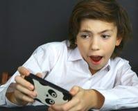 Juego de ordenador del juego del muchacho en su teléfono celular Imágenes de archivo libres de regalías