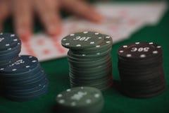 Juego de póker en manos del ` s de los hombres en la tabla verde Imágenes de archivo libres de regalías