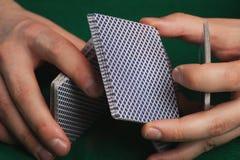 Juego de póker en manos del ` s de los hombres en la tabla verde Fotografía de archivo libre de regalías