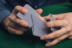 Juego de póker en manos del ` s de los hombres en la tabla verde Foto de archivo libre de regalías