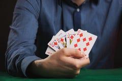 Juego de póker en manos del ` s de los hombres en la tabla verde Imagen de archivo libre de regalías