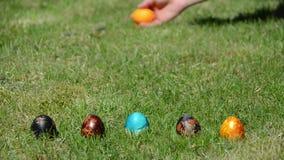 Juego de Pascua de la familia con los huevos coloridos pintados en hierba Fotos de archivo