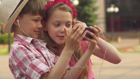 Juego de pequeños niños con smartphone al aire libre almacen de video