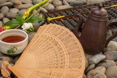 Juego de té chino, ábaco, fan china, flores colocadas en bloques del granito foto de archivo