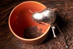 juego de té chino negro seco, con el primer del tamiz, las tazas y la tetera en fondo sobre viejo tablero de madera imagen de archivo libre de regalías