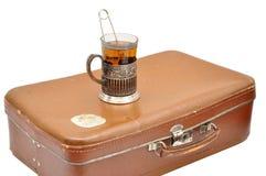 Juego de té con el vidrio-tenedor y la maleta vieja aislados Fotografía de archivo libre de regalías